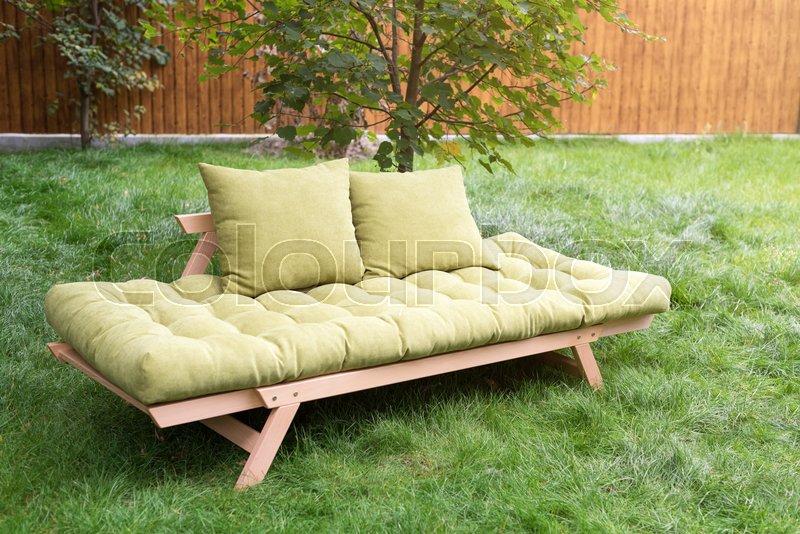 Green sofa in the yard outdoors. Outdoor furniture in green garden patio, stock photo