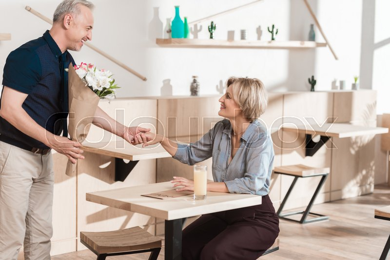 Man presenting a bouquet of flowers to woman at cafe, stock photo