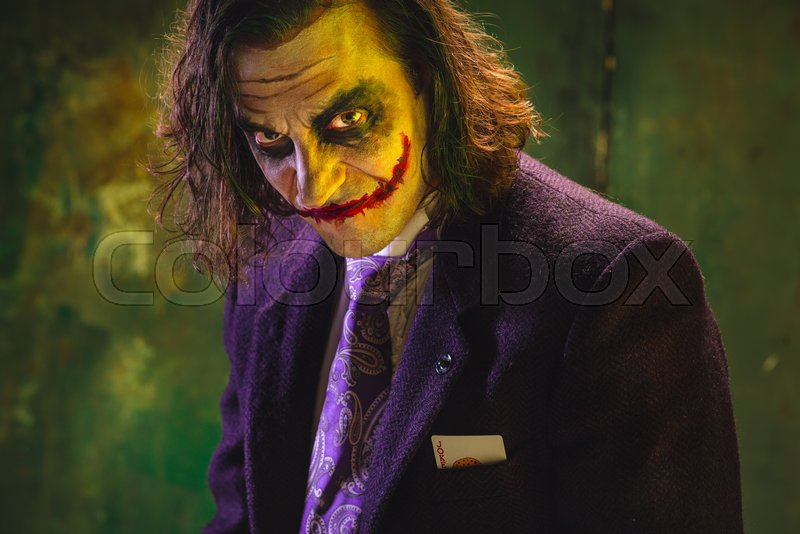 Bloody Halloween theme: The crazy maniak face on dark studio background, stock photo