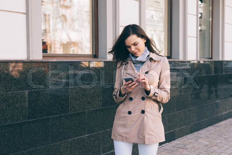 Young slim woman in a beige coat walks down the street and checks the mobile phone, stock photo