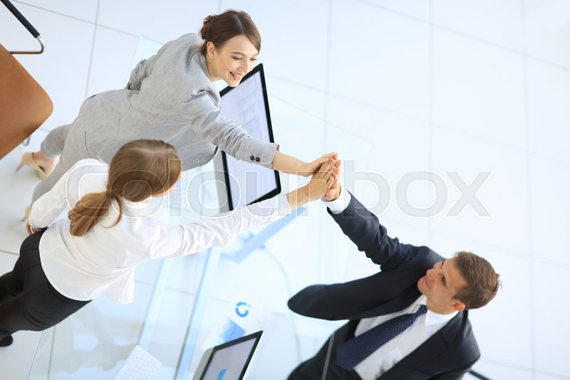 View from the top.members of the business team giving each other a high five above the Desk, stock photo