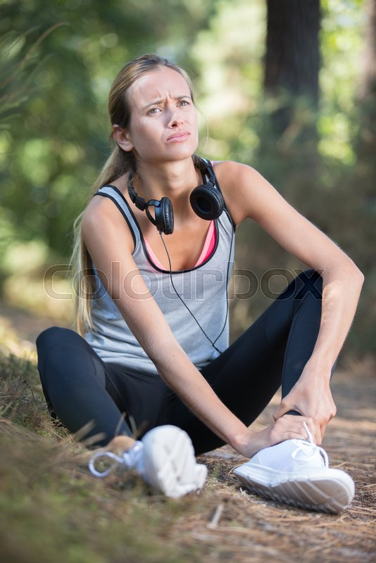 Fitness woman suffering painful ankle sprain injury, stock photo