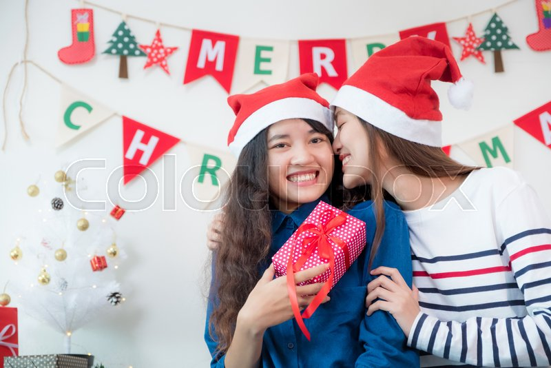 Asia lover Girlfriend kiss cheek and give Christmas gift at xmas party,Asia girl friends wear santa hat exchange red gift box with smiling face,gift giving,Lovely lesbian couple, stock photo