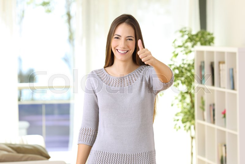 Front view portrait of a satisfied home owner looking at camera standing in a house interior, stock photo