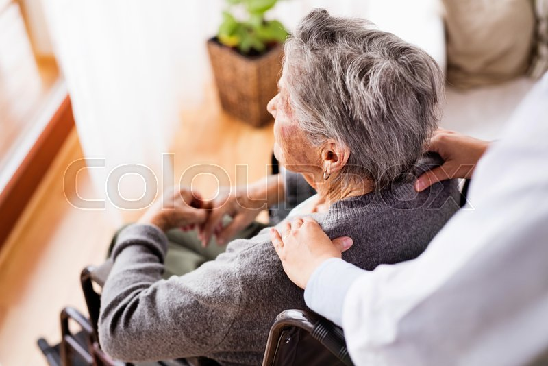 Health visitor and a senior woman during home visit. Unrecognizable nurse giving woman shoulder massage, stock photo