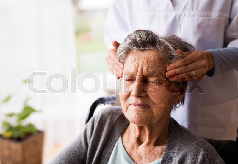 Health visitor and a senior woman during home visit. Unrecognizable nurse giving woman temple massage, stock photo