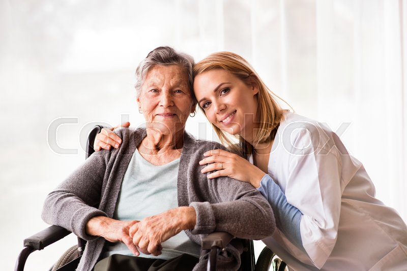 Health visitor and a senior woman during home visit. Portrait of a nurse and an elderly woman in an wheelchair, stock photo