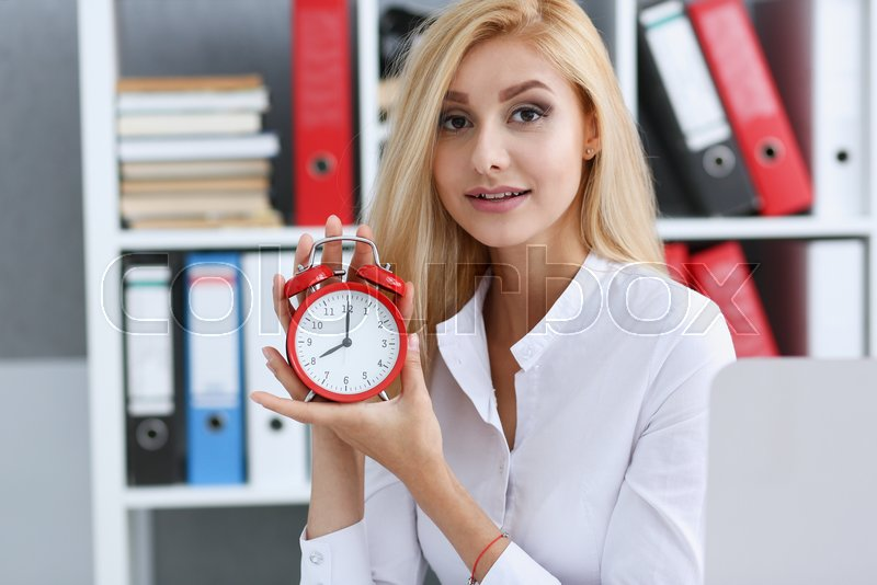 Smiling business woman holding in hand on the alarm clock a red color showing eight o\'clock in the morning or evening AM PM, stock photo