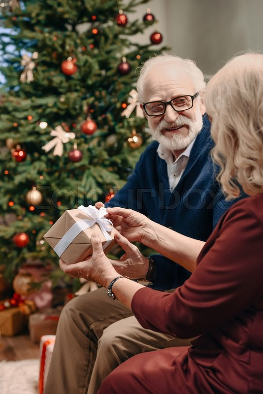 Happy senior man presenting christmas gift to wife in front of beautiful christmas tree, stock photo