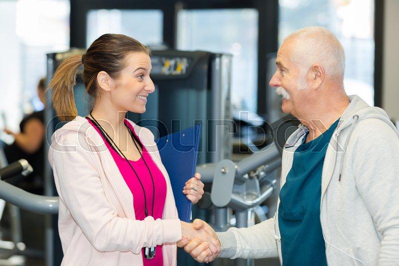 Female coach meeting senior man client at the gym club, stock photo