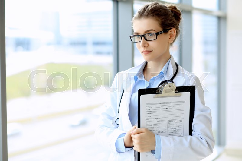 Medical physician doctor woman over blue clinic background, stock photo