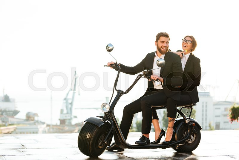 Full length side view image of laughing business couple sitting on modern motorbike in park and looking at the camera, stock photo