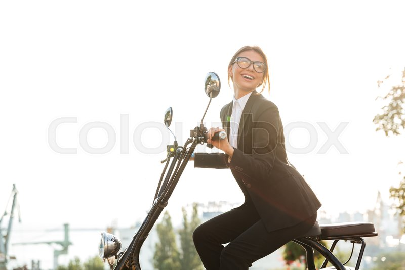 Side view of laughing business woman sitting on modern motorbike outdoors and looking away, stock photo