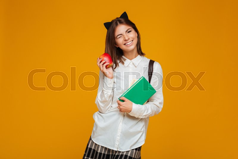 8d67b3af22ad Portrait of a pretty schoolgirl holding books with apple and winking  isolated over orange background