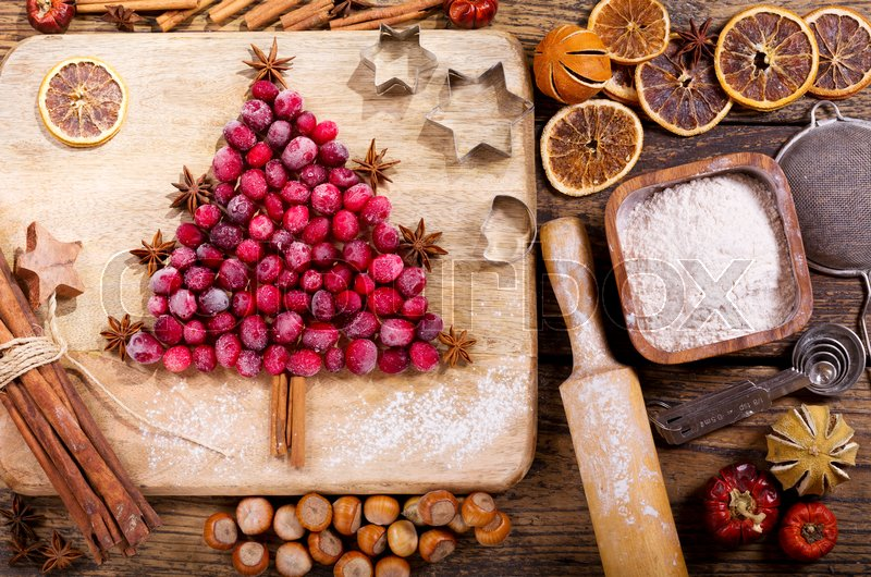 Christmas food. Ingredients for cooking Christmas baking: fir tree made from frozen cranberries, kitchen utensils and dried fruits on a wooden table, top view, stock photo