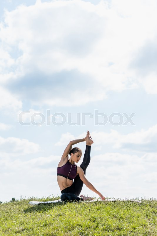 Young woman standing on one leg with other raised practicing yoga outdoors, stock photo