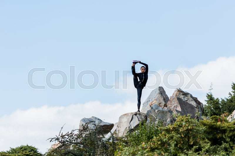 Young woman standing on one leg with other raised practicing yoga outdoors on rocks, stock photo