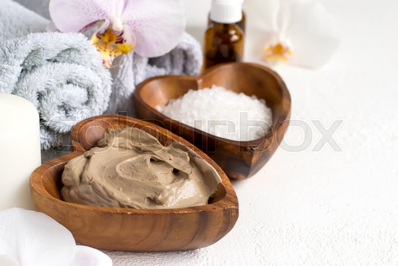 Spa setting with cosmetic clay mask for body and face, Towel and Essential oil , stock photo