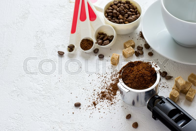 Ingredients for coffee: ground coffee in the horn of the coffee machine, sugar and a cup. Top view with copy space, stock photo