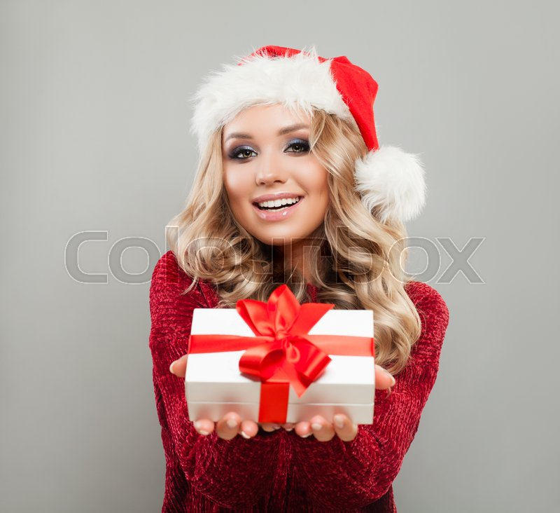 Christmas Woman in Santa Hat Holding White Xmas Gift Box with Red Ribbon. Happy Model with Blonde Hair, Makeup and Christmas Gift. New Year or Christmas Concept, stock photo
