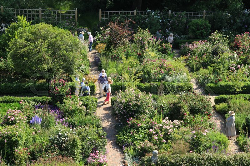 Many tourists are walking in one of the gardens with blooming ...