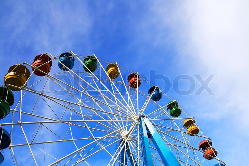 Roundabout - a big color wheel against the background of the blue cloudy sky, stock photo