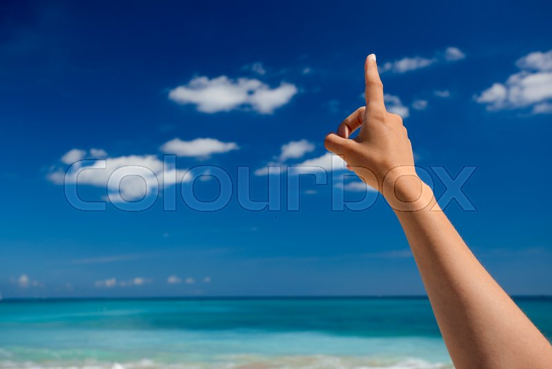 Female hand against a beautiful blue sky pointing somewhere, stock photo