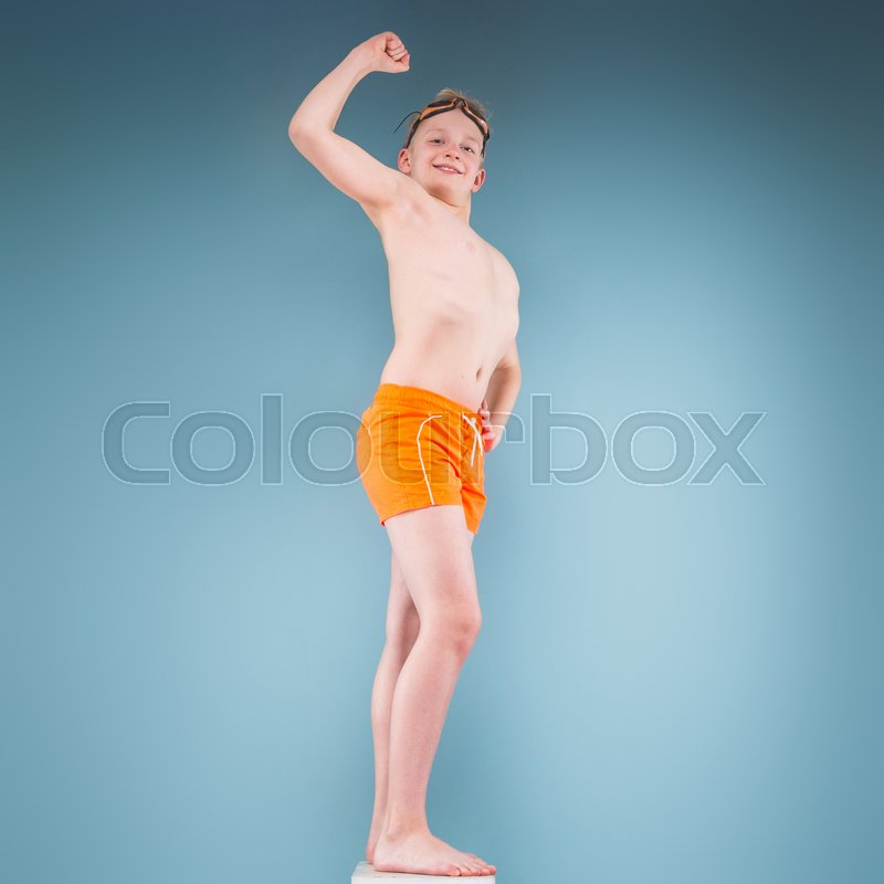 2d5289eb6f Stock image of 'Isolated on grey, teenage blond caucasian boy in orange  shorts and