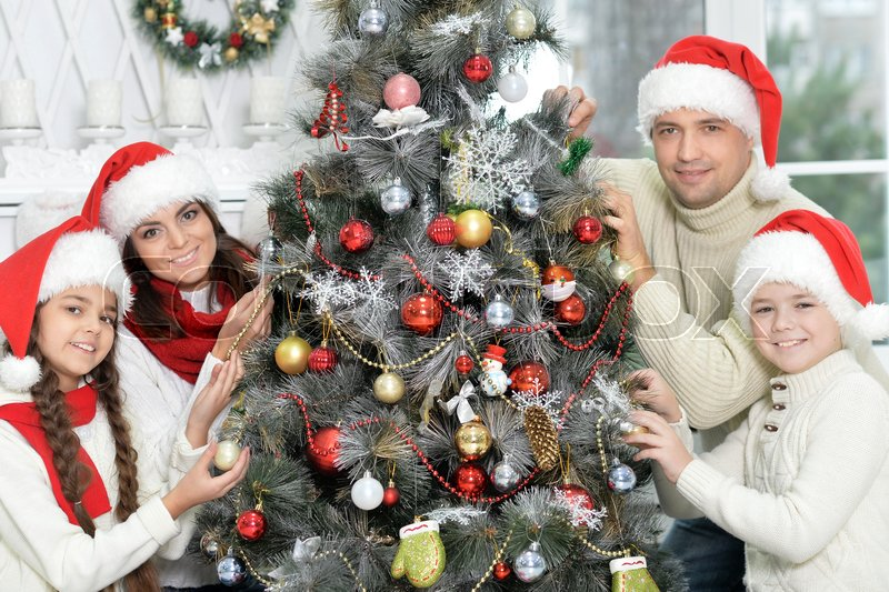 Portrait of smiling family decorating Christmas tree together and looking at the camera, stock photo