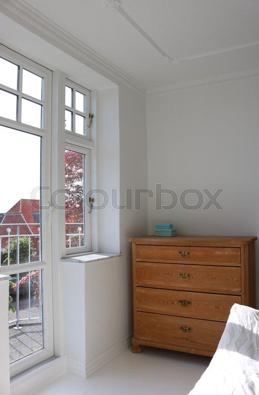 Soveværelse med afsyret kommode ved sprossevindue og dør ud til ...