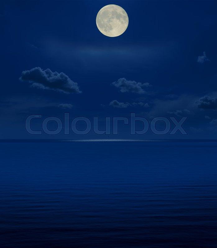 Full moon in night over sea, stock photo