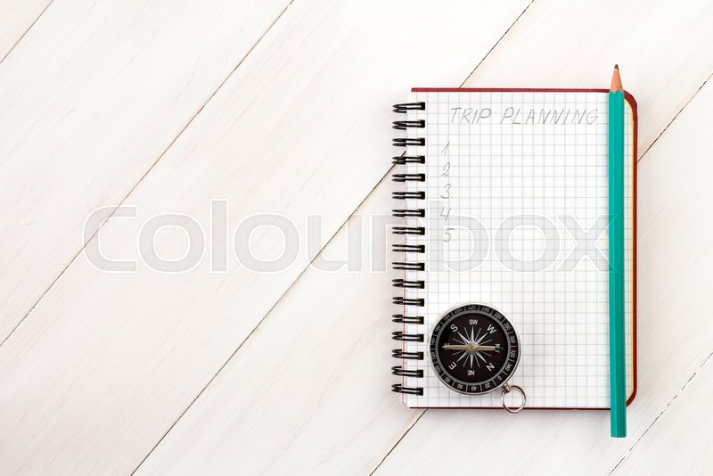 Traveler\'s notebook with compass and pencil on wooden background, stock photo