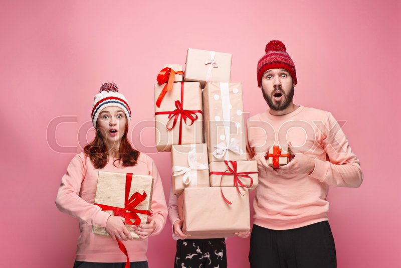 Father and mother give gifts to little daughter at pink studio background, stock photo