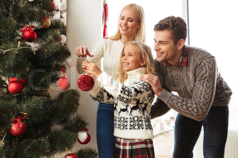 Happy family decorating christmas tree at home, stock photo