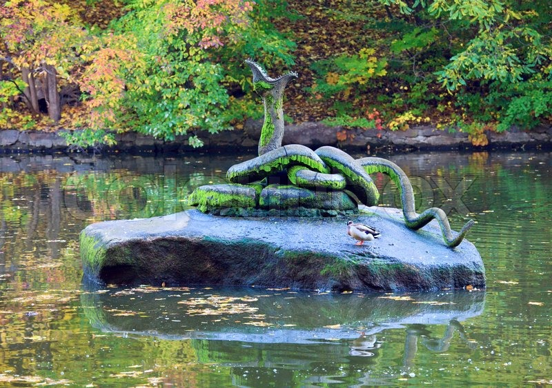 Artificial serpent on stone in pond centre in autumn park for Artificial pond water