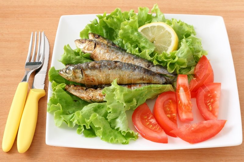Stock image of fried sardines with salad