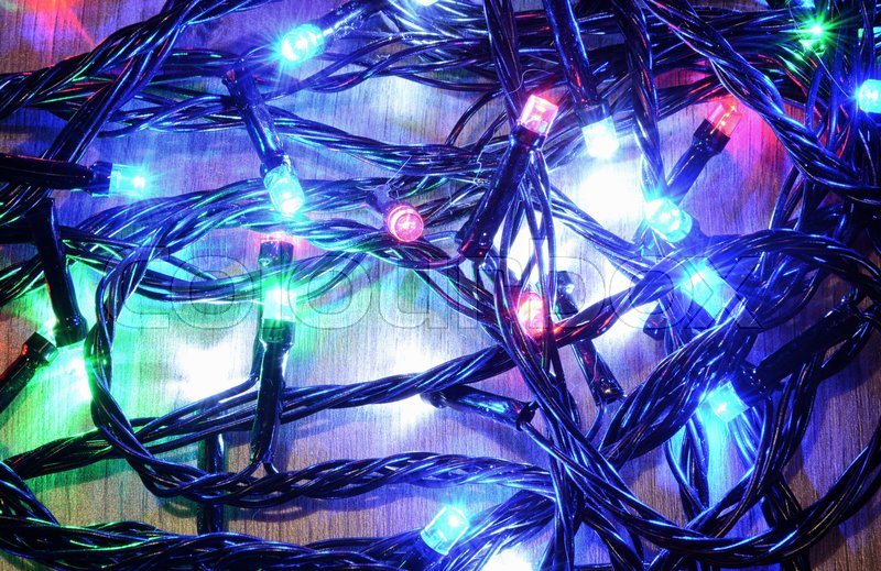 New-year electric garland on a wooden background. Bright bulbs on a wooden table and sprigs of a Christmas tree, stock photo