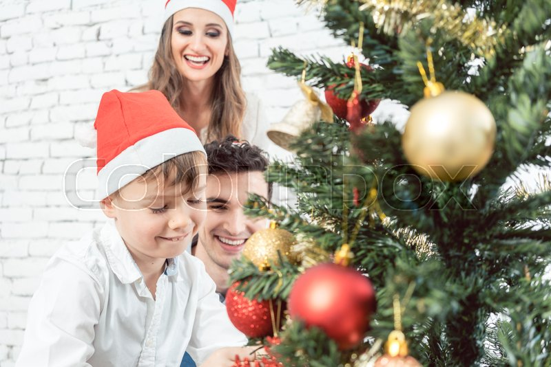 Family decorating the Christmas tree with Christmas decorations , stock photo
