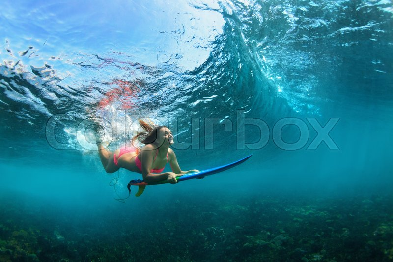 65c41c076d Active girl in bikini in action. Surfer woman with surf board dive  underwater under breaking big wave. Teenage lifestyle. Water sport