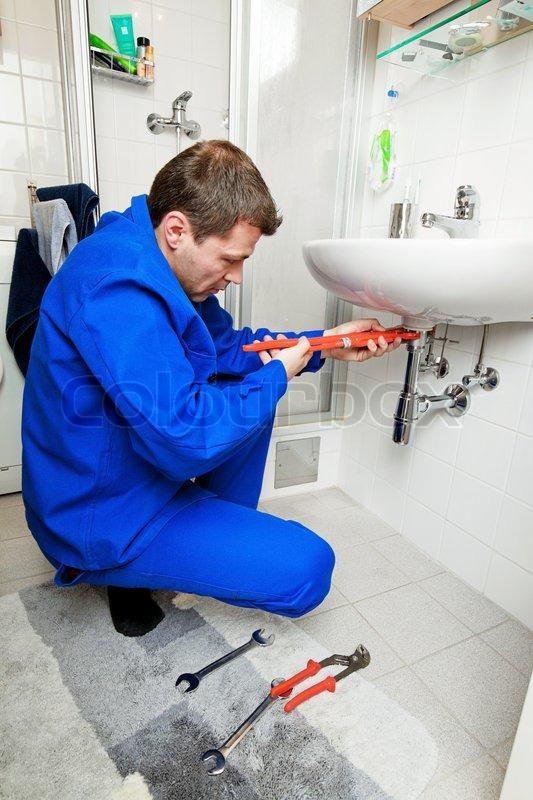 A Plumber Repairing A Broken Sink In Bathroom, Stock Photo