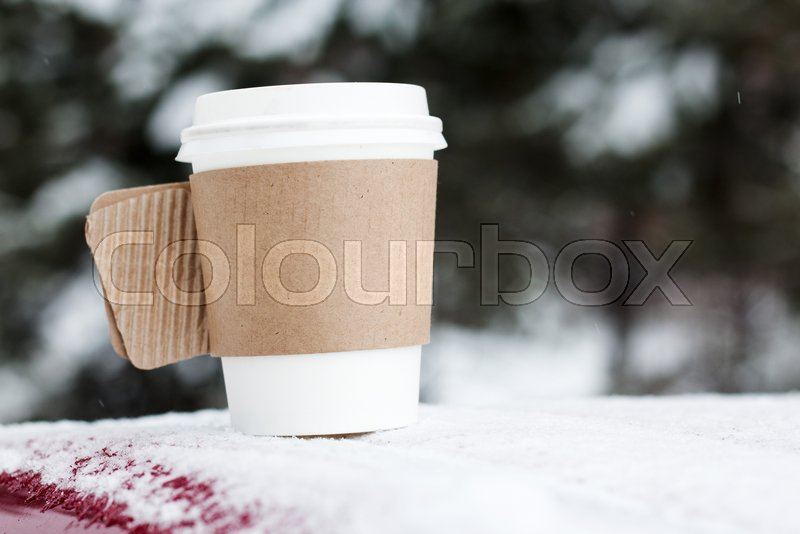 Steaming Cup of Hot Coffee or Tea standing on the Outdoor Table in Snowy Winter Morning. Cozy Festive paper cupwith a Warm Drink in Winter Garden. Christmas Morning Concept , stock photo