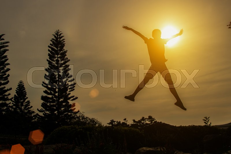 Silhouette of happy people jumping in sunset, stock photo