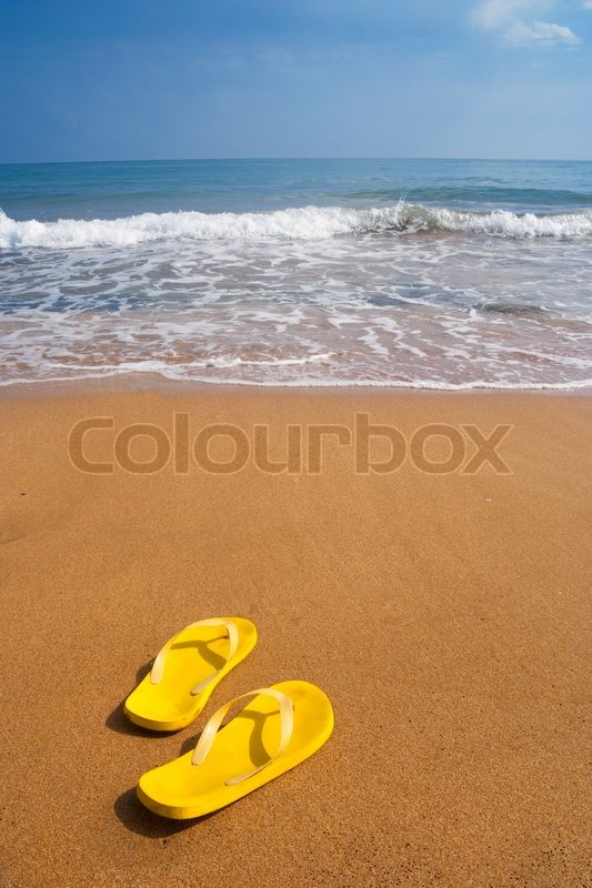 Stock image of 'Yellow beach slippers on sandy beach, summer, bathing'