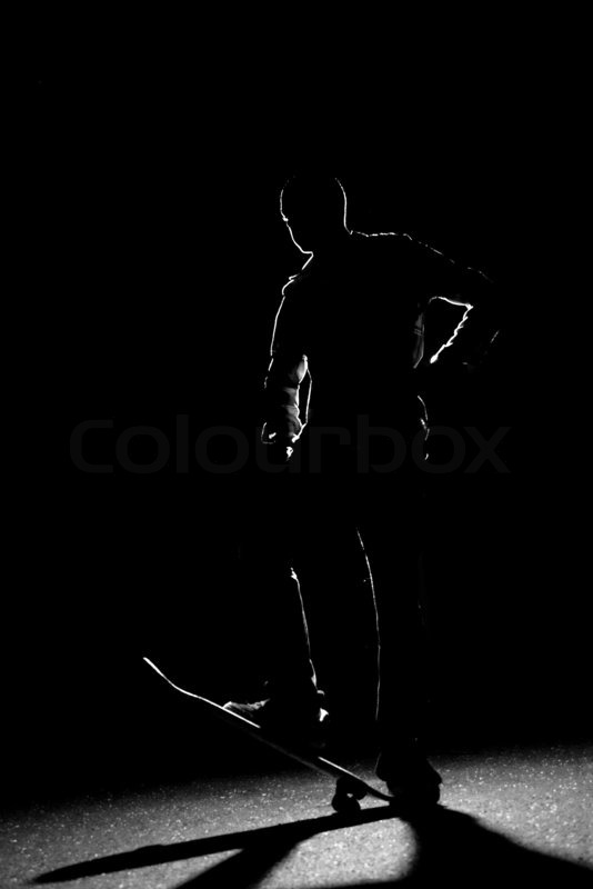 A rim lit skateboarder guy posing under dramatic back lighting with his skateboard flipped up in the front, stock photo
