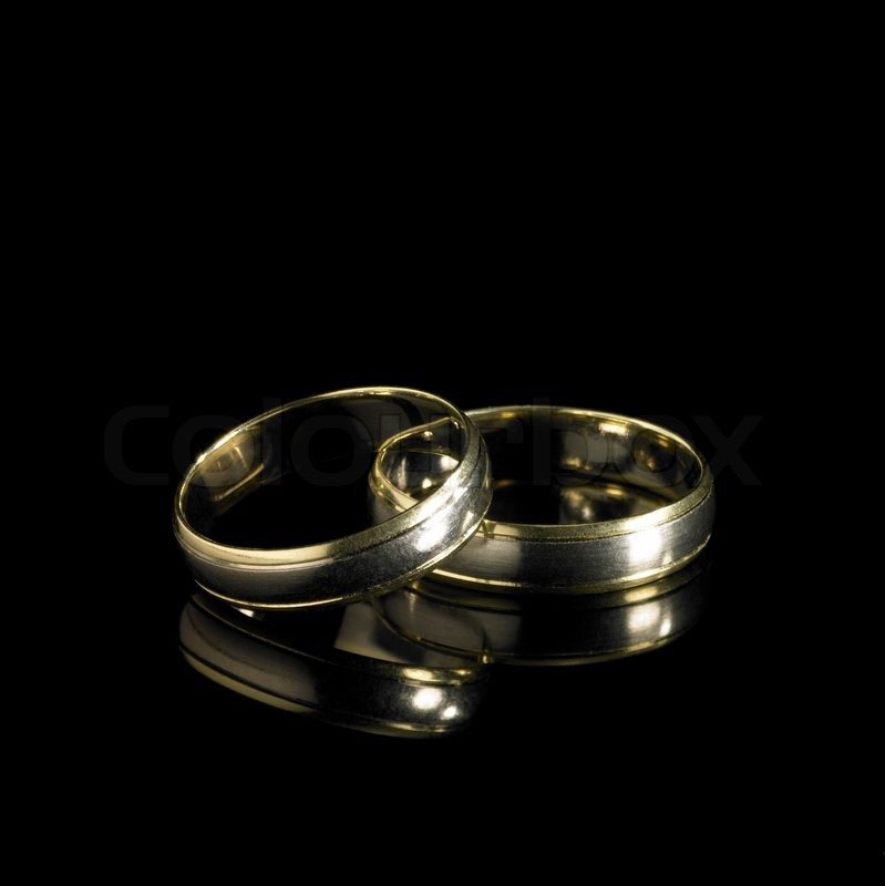 studio photography of 2 golden wedding rings in black