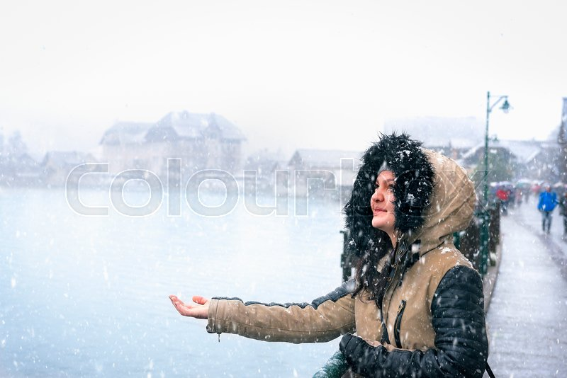 Portrait of a beautiful woman dressed for cold weather, enjoying the snowfall with her hand stretched to catch snowflakes, in the famous Hallstatt town, Austria, stock photo