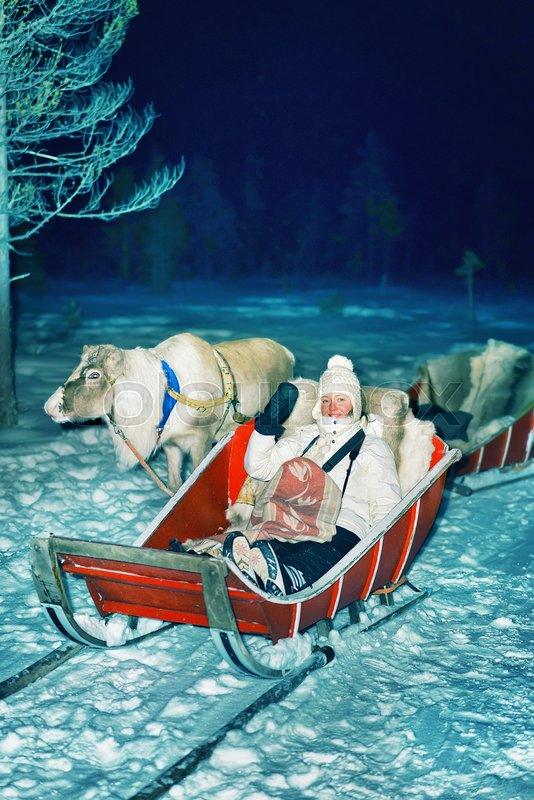 Girl with reindeer sleigh at night safari in the forest, Rovaniemi, Lapland, Finland. Toned, stock photo