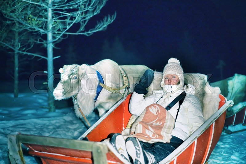 Girl in reindeer sleigh at night safari in the forest, Rovaniemi, Lapland, Finland. Toned, stock photo