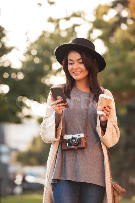 Charming asian tourist woman texting message on mobile phone while holding coffee cup in public park, stock photo