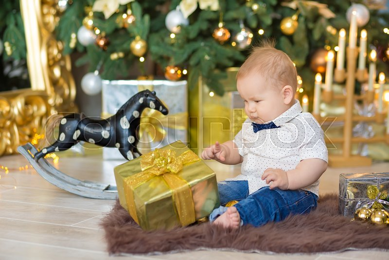 Beautiful little baby boy celebrates Christmas. New Year\'s holidays. Baby in a Christmas costume casual clothes with gifts on fur close to new year tree in studio decorations, stock photo